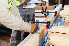 Building a wall for frame house. Worker make marks for cutting timber. Royalty Free Stock Photos
