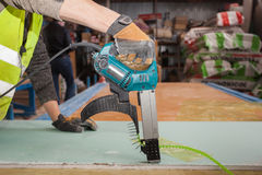Building a wall for frame house. Worker use autofeed screwdriver for attaching drywall. Building a wall for frame house. Worker use autofeed screwdriver for royalty free stock photos