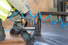 Building a wall for frame house. Worker use autofeed staple gun for attaching a vapor barrier. Building a wall for frame house. Worker use autofeed staple gun royalty free stock photos