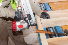 Building a wall for frame house.Worker use Framing Nailer to attach wooden beams. Building a wall for frame house.Worker use Framing Nailer to attach wooden royalty free stock photo