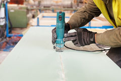 Building a wall for frame house. Worker use Laminate Trimmer for cutting drywall. Royalty Free Stock Photo
