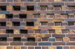 Building wall made of dark, yellow to brownish clinker bricks with various alternating patterns. The stones are offset in rows,. Turned, indented or omitted for royalty free stock photo
