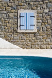Building wall and pool. A thick stone wall and shuttered window next to a swimming pool Stock Image