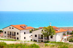Building of white houses with brown roofs. Building of new two-storey white houses with brown roofs and balcony on coast Stock Images
