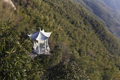 Building of white stone pavilion halfway up the mountain. Halfway up the hill, forests, rocks and the top of the mountain, blue, volley, trees, plants, bamboo Stock Images