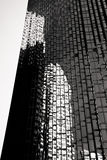 Building of windows in black and white. Office building with glass reflecting additional buildings Stock Photos