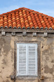 Building With Orange Roof Tiles And Wodden Shuttered Window Stock Photography