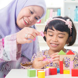 Building wooden house. Muslim family building wooden house toy. Southeast Asian family living lifestyle Stock Photography