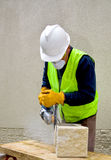 Building worke with angle grinder. Building worker in safety gear with angle grinder cutting concrete block Royalty Free Stock Photography