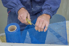 Building worker cutting plastic grid with cutter Royalty Free Stock Images