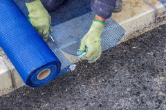 Building worker cutting plastic grid Royalty Free Stock Photography