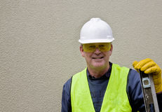 Building worker in safety gear. Building worker in fluorescent jacket and full safety equipment Royalty Free Stock Photo