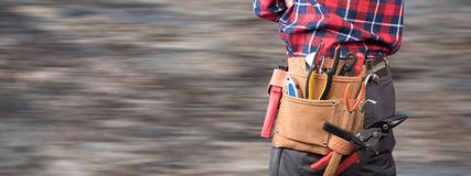 Building worker with tool belt. On blurred background stock image