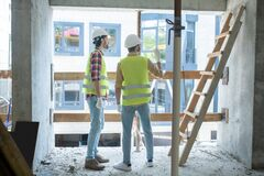 Free Building Workers In Yellow Vests And Gloves Standing Back To Camera Near The Window, Discussing Something Royalty Free Stock Photography - 186752567