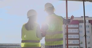 Building workers working at construction site, builders looking in blueprint, back view, copy space. Building. Development, teamwork and people concept stock video footage