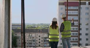 Building workers working at construction site, builders looking in blueprint, back view, copy space. Building. Development, teamwork and people concept stock video