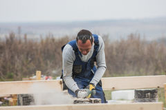Building working - adult man with circular saw outdoors, small business Royalty Free Stock Photography