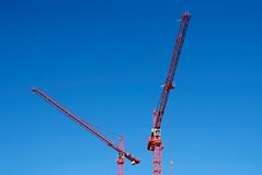 Building works. Two red cranes and building works royalty free stock photography