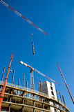 Building yard. Scene of a modern building under construction with cranes, scaffolds, prefabricated element and concrete structure against a limpid sky Royalty Free Stock Photo