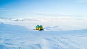 Lonely colorful house in the middle of nowhere in winter Iceland white snow blue sky. Building yellow and green color lonely house in the middle of the snow royalty free stock photo