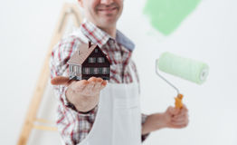 Building your house. Painter holding a model house and smiling: home renovation and remodeling concept Stock Image