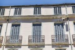 Buildinga francés típico con las ventanas antiguas en Nimes, Francia Imagen de archivo