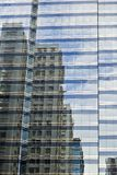 Buildings. Reflections of residential buildings on a commercial building Stock Photos