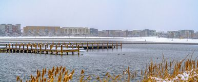 Buildings against sky on a snow covered landscape beyond the lake in winter. Snowy wooden decks can also be seen above the water with grasses in the foreground royalty free stock photos