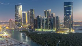 Buildings on Al Reem island in Abu Dhabi day to night timelapse from above. Skyscrapers on Al Reem Island in Abu Dhabi day to night transition timelapse after stock footage