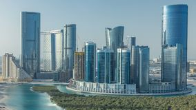 Buildings on Al Reem island in Abu Dhabi timelapse from above. Aerial citiscape of Al Reem Island at morning, showing the reflection on skyscrapers stock footage