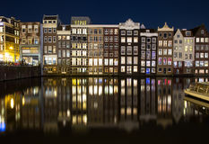 Buildings along the Damrak at Night in Amsterdam Royalty Free Stock Photography