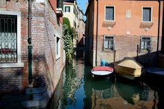 Buildings and boats on narrow canal in Venice, Italy Stock Photos