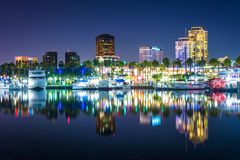 Buildings and boats reflecting in the harbor at night  Stock Images
