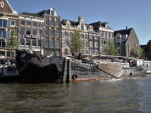 Buildings, canal and a boat in Amsterdam Royalty Free Stock Images