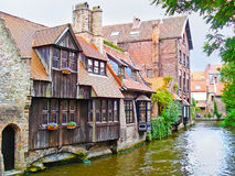 The buildings on canal. The row of the old brick mansions with wooden balconies, standing on Den Dijver Canal, at Bonifacius Bridge, Bruges, Belgium stock photos