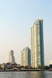Buildings on Chaophraya riverside in evening Stock Images