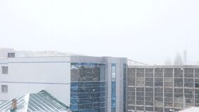 Buildings in the city in heavy snow storm. Slow motion stock video footage