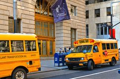 Buildings, classic architecture, yellow school bus with driver on the street in wall street in manhattan in new york royalty free stock images