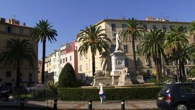 Street In Corsica panning shot. Buildings in Corsica with large building and palm trees stock footage