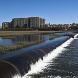 Buildings and the dam. Buildings near a riverside, facing a dam Royalty Free Stock Photos