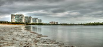 Buildings in the distance on Marco Island, Florida, beach. Under an overcast sky in winter royalty free stock photos
