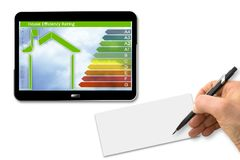 Buildings energy efficiency concept image. 3D render of a digital tablet with home and energy classes according to the new Europe. An law and hand drawing on a stock image