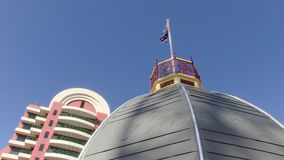 Buildings and flagpole of United Kingdom. A worms eye view shot of blue sky with a flag pole of United Kingdom stock footage