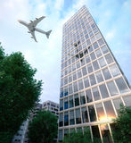 buildings with flying airplane and trees concept business and tourism background Royalty Free Stock Images