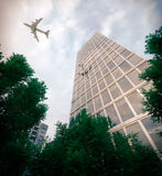 Buildings with flying airplane and trees concept business and tourism background Royalty Free Stock Photography