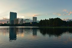 Buildings and forest reflected in lake in beautiful sunset at Eola Lake Park. stock photo