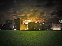 Buildings and green grass field Stock Images