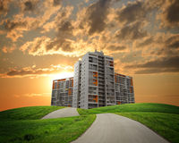 Buildings, green hills and road against dramatic Stock Photos