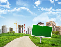 Buildings, green hills and road with empty Royalty Free Stock Photo