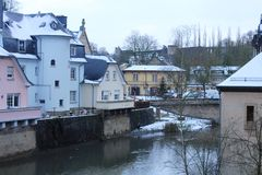 Winter in Luxemburg City. Buildings in Grund, district of Luxemburg City,  under snow. Mosel river in the center of the city Stock Images